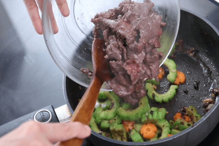 Chúng ta xào chung thịt bò và khổ qua sao cho đều tay thì gia vị sẽ đậm đà và hòa quyện